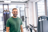 Smiling man surrounded by gym equipment. - 180224814