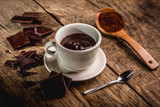chocolate cup on wooden table with dark chocolate and powder - 180225615
