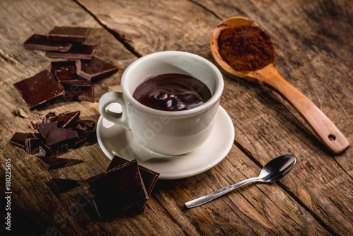Fototapeta chocolate cup on wooden table with dark chocolate and powder