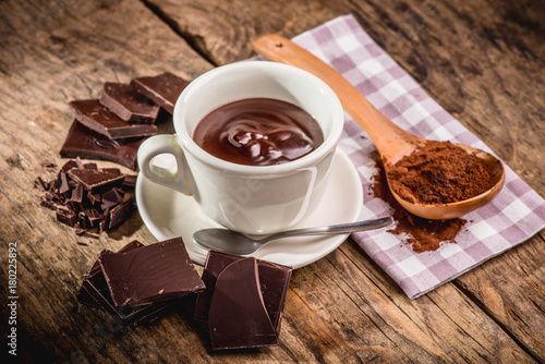 Foto op Canvas Chocolade chocolate cup on wooden table with dark chocolate and powder