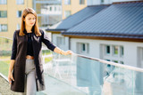 Female serious freelancer business woman in black sleeveless jacket standing and thinking on terrace outdoor. Education, lifestyle and people concept. - 180230212
