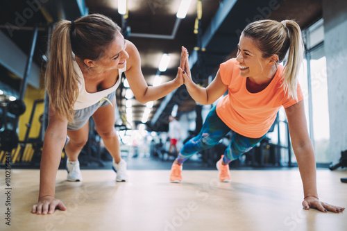Two sporty girls doing push ups in gym - 180236443