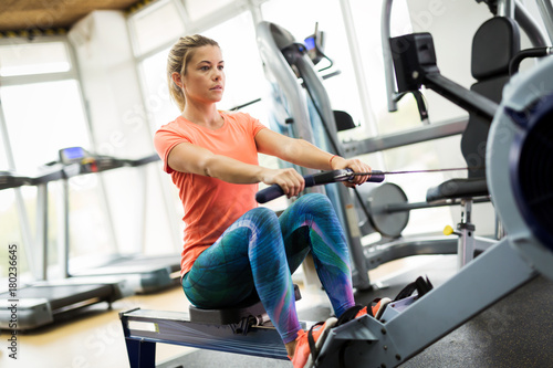 Wall mural Young blonde woman working on rowing machine