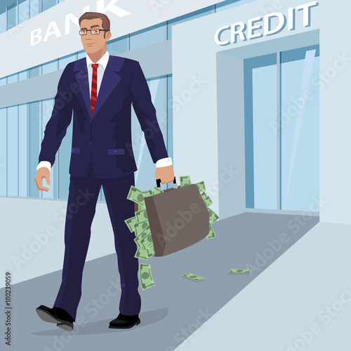 Satisfied young businessman in blue business suit leaves building with inscription Credit, with briefcase full of cash money. Man on background of bank facade
