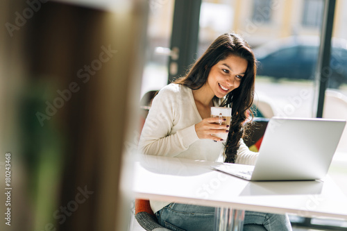 Poster Brunette studying and enjoying coffee