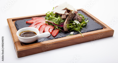 Fotobehang Steakhouse Perfectly fried or grilled steak. Sliced Beef steak , served with green salad leaves and Barbecue sauce on wooden cutting board