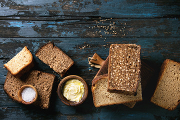 Variety loaves of sliced homemade rye bread whole grain and seeds for breakfast with olive wood bowls of butter and salt over old dark wooden background. Top view, copy space.