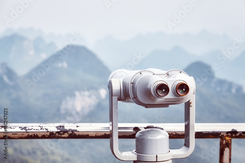 Wall mural Vintage toned picture of tourist binoculars pointing at karst formations around Guilin. It is one of China most popular tourist destinations. Selective focus.