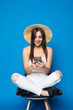 Pretty woman with long hair in hat chilling in chair on blue background and typing on phone.