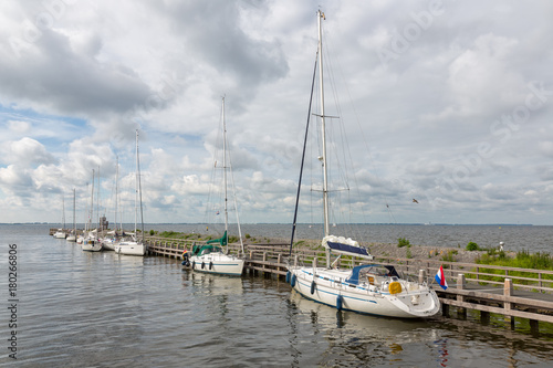 Fotobehang Pier Harbor of historic Dutch village Urk with modern sailing yachts moored to a pier
