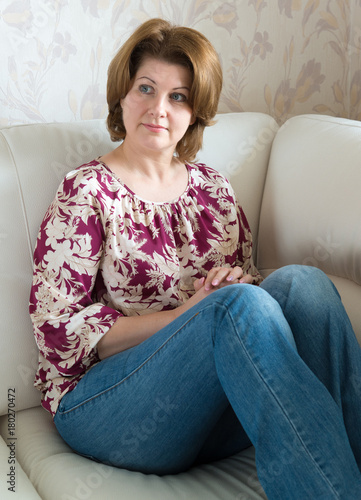 Poster Woman sitting on white sofa in the room