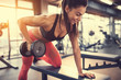 Leinwanddruck Bild - Sportswoman in gym exercise muscles