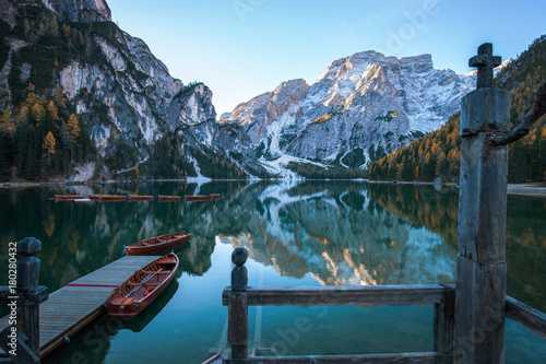 Deurstickers Bergen Idyllischer Bergsee mit Anlegesteg und Booten vor malerischer Felslandschaft