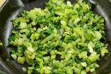 Chopped bok choy sauteed in olive oil in cast iron frying pan skillet - 180285662