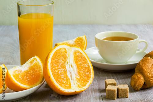 Fotobehang Sap A glass of orange juice, a sliced orange and a cup of tea with a croissant and pieces of cane sugar - a healthy diet concept, a light breakfast