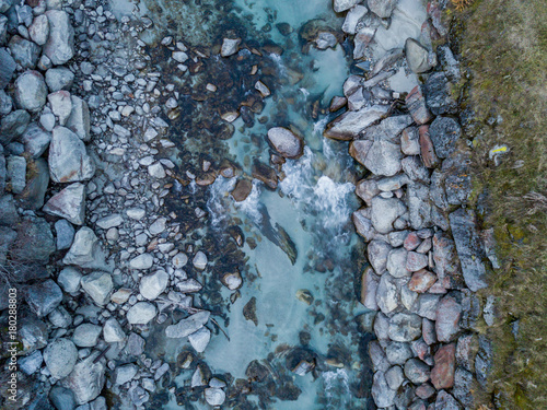 Fotobehang Stenen Aerial view of river flowing between rocks, close up