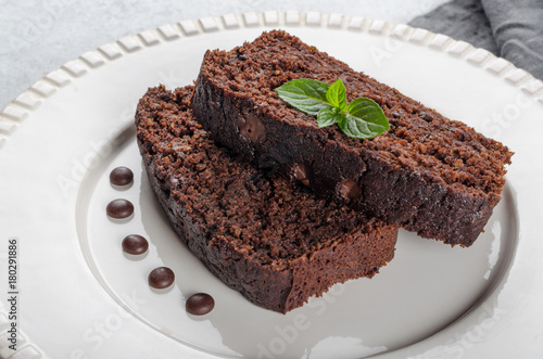 Foto op Canvas Chocolade Two slices of chocolate cake with mint leaves served on a white