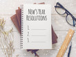 Notebook with New's Year Resolutions massage, glasses and working ornament on white wooden table background.