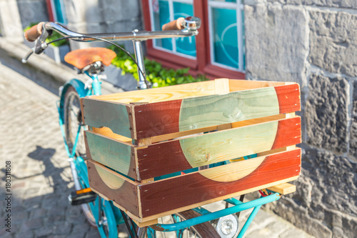 Fotobehang Fiets retro style bicycle parks outside near old European stone wall and shop window