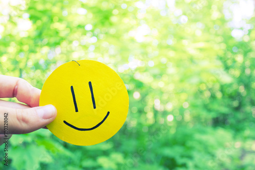 yellow smile on green leaves background Poster