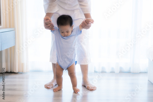 Happy Asian little baby boy learning to walk with mother help in bedroom at home Poster