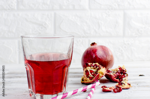 Foto op Plexiglas Sap Pomegranate juice in glass and pomegranates on white wooden background