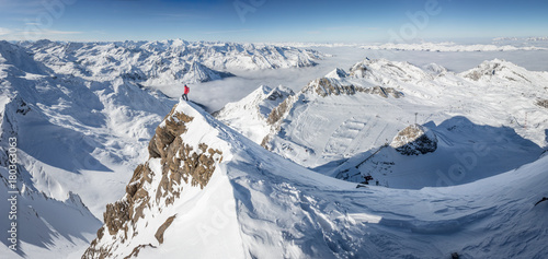 Foto op Canvas Bleke violet Mountaineer standing on a snow capped mountain summit