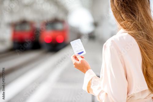 Trzymając bilet z pustej przestrzeni z pociągami na tle na stacji kolejowej