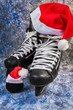 Hockey men's skates and puck close-up with Santa cap, concept of Christmas winter tournaments on a blue background