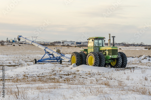 Fotobehang Trekker Green tractor and grain loader on the snow field