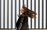 Stylu życia portret ładny potomstwo model w okularach przeciwsłonecznych z włosianym dmuchaniem w wiatrowym odprowadzeniu przy ulicą