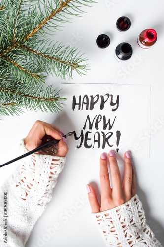 Fototapeta Girl writing Happy new year calligraphy card