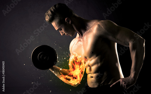 Wall mural Bodybuilder athlete lifting weight with fire explode arm concept
