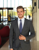 Portrait of happy young businessman standing in hotel lobby. - 180412851