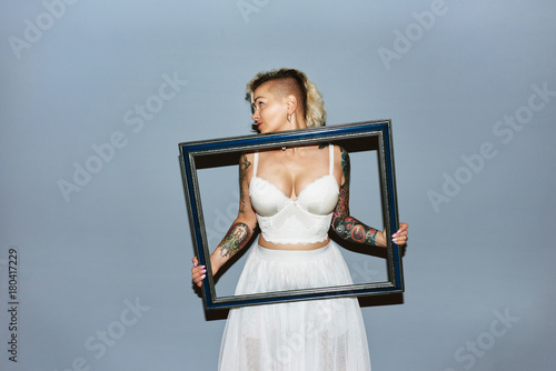 Freaky blond girl with picture frame bringing attention to breasts Poster