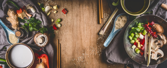 Vegetarian Asian cuisine ingredients for stir fry with chopped vegetables, coco milk, spices,chopsticks and wok pot on rustic wooden background, top view, banner. Chinese or Thai food cooking © VICUSCHKA