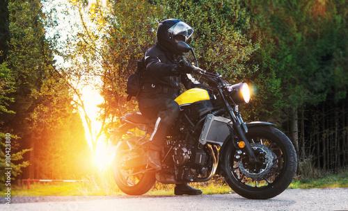 Motorrad-Fahrer auf Landstrasse im Sonnenlicht vorm Wald
