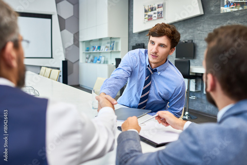 Portrait of young successful businessman shaking hands with partners at meeting table in board room greeting each other before negotiations