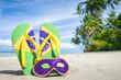 Quadro Brazil flag flip flops with carnival mask on palm fringed Brazilian beach.