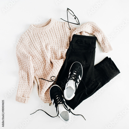Fashion winter women clothes look on white background. Flat lay, top view. Sweater, sneakers, jeans and glasses.