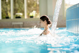 Serene girl enjoying stream of waterfall and its gentle splashes in swimming-pool at spa resort - 180438882