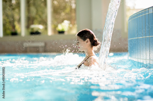 Serene girl enjoying stream of waterfall and its gentle splashes in swimming-pool at spa resort - 180438882