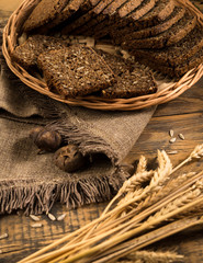 rye bread in a wicker tray with a napkin and spikelets on wooden surface, view from above