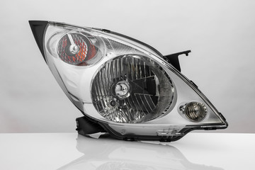 modern automotive headlight with reflection isolated on light background