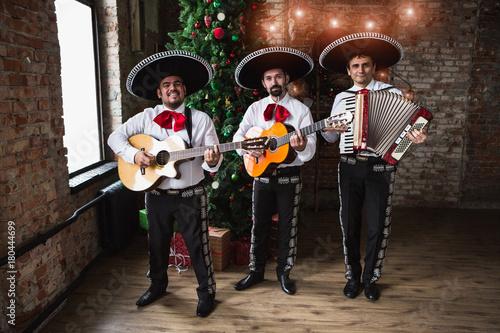 Mexican musicians mariachi near a Christmas tree.