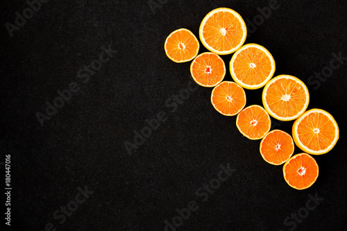 A set of oranges placed diagonally on a black plywood background. - 180447016