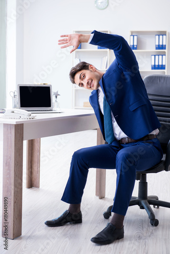 Wall mural Young businessman doing sports stretching at workplace
