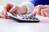 Hands working on accounting calculator calculating profit