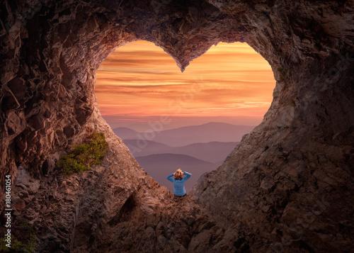 Woman in heart shape cave towards the vast landscape