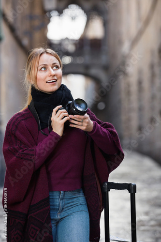 Girl taking picture with camera in the town